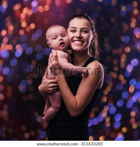 mother and baby in the Christmas bokeh background  - stock photo