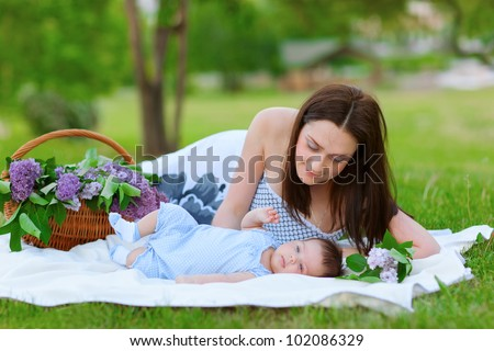 mother and baby resting in summer park with lilac bouquet - stock photo