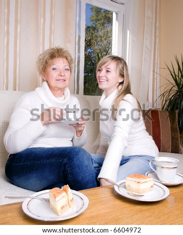 Mother and daughter drinking coffee together - stock photo