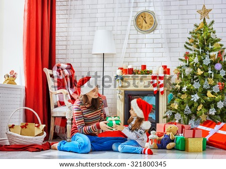 Mother and daughter exchanging Christmas gifts - stock photo