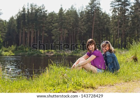 Mother and daughter on the shore of Lake - stock photo