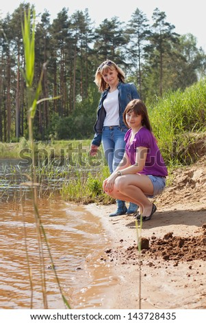 Mother and daughter on the shore of Lake