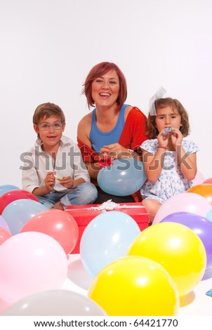 Mother and kids playing with colourful balloons - stock photo