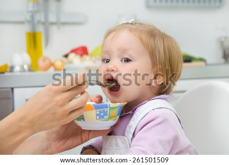 mother feeding baby with a spoon in the kitchen at home - stock photo