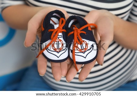 Mother Hand Holding Pink Newborn Baby Booties, New Born Boy - stock photo