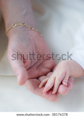 mother holding a baby`s hand in her hand - stock photo
