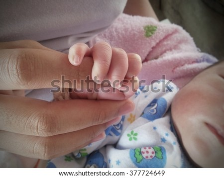 mother holding hand of her baby newborn with soft focus, love and family concept  - stock photo