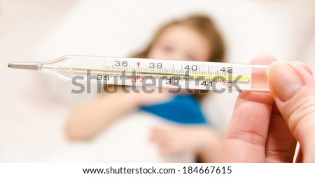 Mother holding thermometer foreground and sick little girl in bed - stock photo