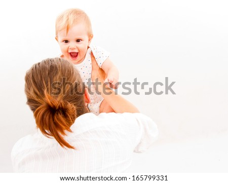 mother raising her baby and laughing isolated on a white background  - stock photo