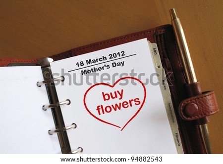 Mother's Day 18 March 2012 in a personal organizer with a note to buy flowers - stock photo