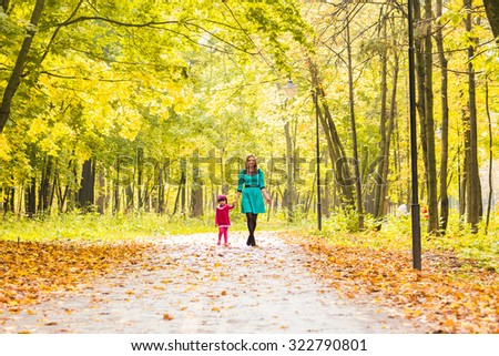 mother with her daughter for a walk in autumn park