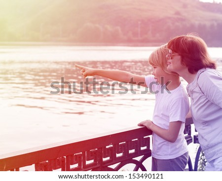 mother with her little son outdoor on the bridge - stock photo