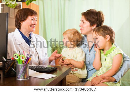 mother with two children and friendly pediatrician doctor at clinic - stock photo