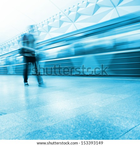 Motion blurred passenger walking in subway station. - stock photo