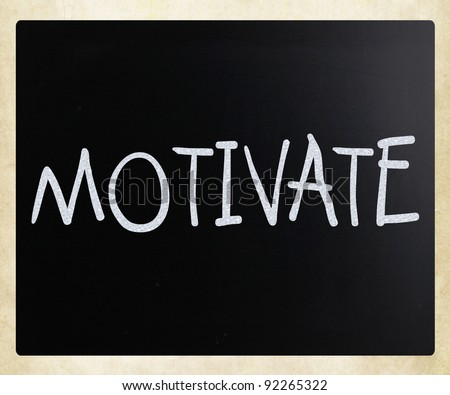 """Motivate"" handwritten with white chalk on a blackboard - stock photo"