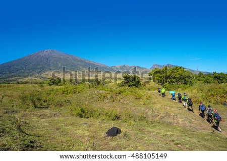 MOUNT RINJANI, LOMBOK, INDONESIA - SEPT 18, 2016: A group of mountaineers walking on savannah field to Sembalun camp site. Rijani mountain is one of the highest mountains in Indonesia