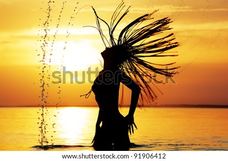 Movement of wet hair of bathing girl against sea sunset - stock photo