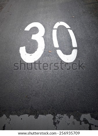 30 mph sign on a tarmac road - stock photo