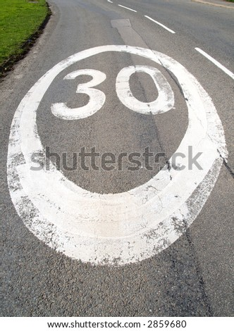 30 mph sign on a tarmac road. - stock photo
