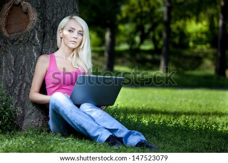21 Mpx full-frame HD-capture.Portrait of a beautiful young blond woman sitting outdoor with laptop
