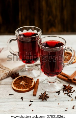 mulled wine with oranges , honey , cinnamon and cloves on a wooden background