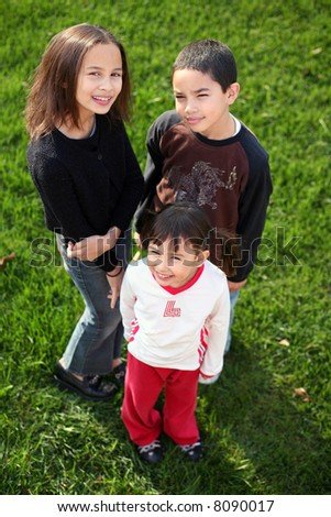 3 multi-racial kids outside in grass - stock photo