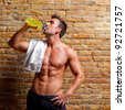 muscle shaped man at gym relaxed drinking energy drink - stock photo