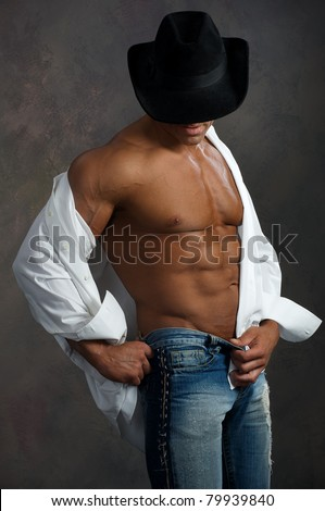 Muscular man in white shirt and black hat on dark background - stock photo