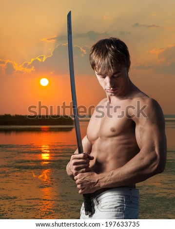 Muscular young man posing with Japanese sword on sunset background - stock photo