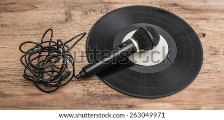 Music background of Microphone on black gramophone Vinyl record on old retro vintage aged wooden table in the closeup Empty space for inscription  - stock photo