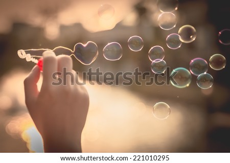 My Heart Bubbles at the sky, sunset,Love in the summer sun with bubble blower,romantic inflating colorful soap bubbles in park - stock photo