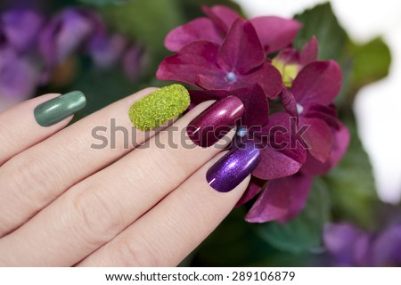 Nail designs with colored sand and dark pearlescent varnishes artificial nails. - stock photo