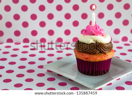 1 neapolitan frosted cupcake on white plate with pink polka dot background and 1 lit birthday candle
