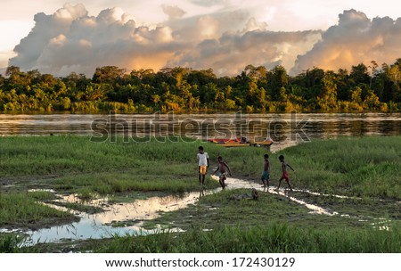 NEW GUINEA, INDONESIA - JUNE 26: Unknown children play on the river bank, near the village. Decline, end of day. June 26, 2012 in  Village, New Guinea, Indonesia  - stock photo