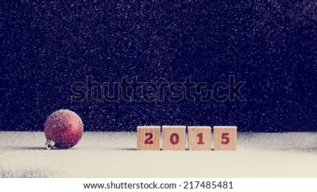 2015 New Year background with snow falling onto a red Christmas bauble and row of four wooden blocks with the date numerals - 2015 - over dark background with copyspace for your seasonal greeting. - stock photo