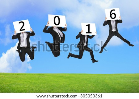 2016 new year business concept, Business man happy holding billboard and jumping or running on the green grass - stock photo