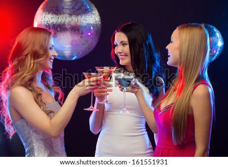 """new year"", celebration, friends, bachelorette party, birthday concept - three women in evening dresses with cocktails and disco ball"