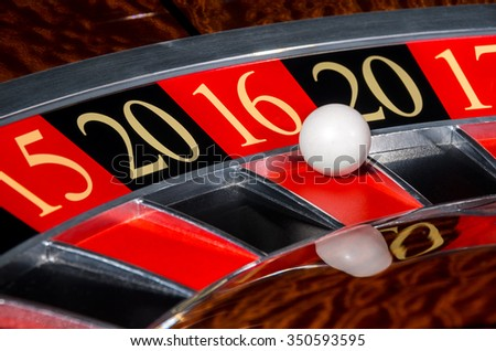 2016 New Year classic casino roulette wheel with red sector sixteen 16 and white ball and sectors 20, 15, 17 - stock photo