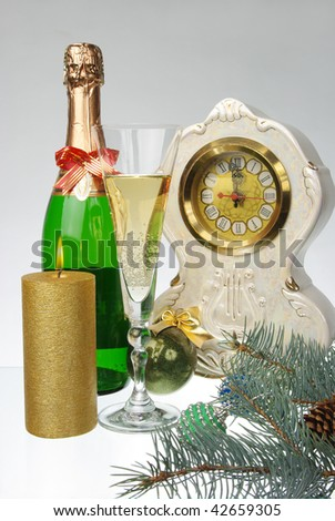 New Year composition. Glass of champagne, bottle, candle, clock and christmas balls