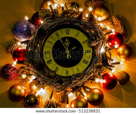 New Year hand made Concept. Time Nearly Twelve O'clock Midnight. Christmas clock in wreath and garlands of colored light bulbs with craft decorations.