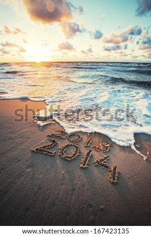 New Year 2014 is coming concept - inscription 2013 and 2014 on a beach sand, the wave is covering numbers 2013. - stock photo