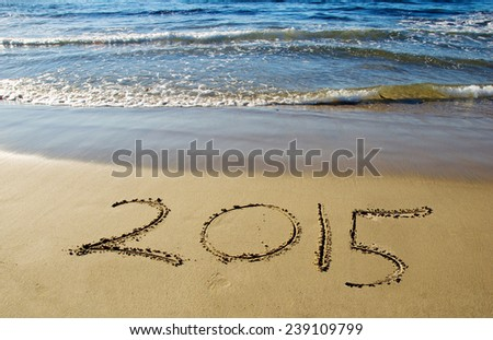 2015 new year written in sand on the beach - stock photo