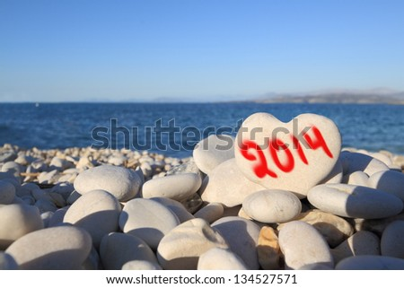 2014  new year written on heart shaped stone on the beach with spray brush - stock photo