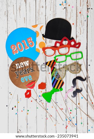 2015 New Years Eve photo booth party background with a festive array of clothing accessories for fun fancy dress on a rustic white wooden panel and copyspace below - stock photo