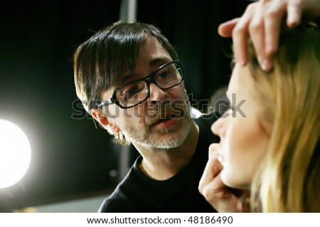 NEW YORK - FEBRUARY 15: Stylist is backstage at the TADASHI SHOJI Collection for Fall/Winter 2010 during Mercedes-Benz Fashion Week on February 15, 2010 in New York. - stock photo