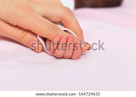 Newborn baby is held by the hand the parent. Care and support. - stock photo