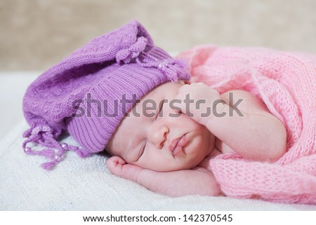 newborn girl in a violet hat sleeps under a pink cape - stock photo