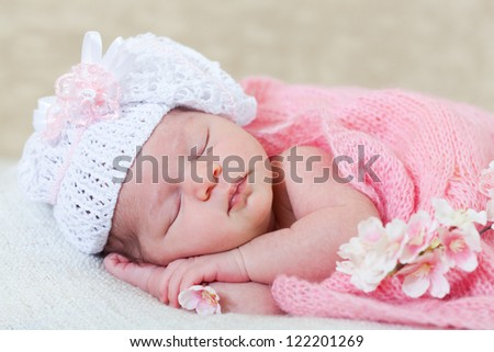 newborn girl sleeps with spring flowers under a knitted pink cape - stock photo