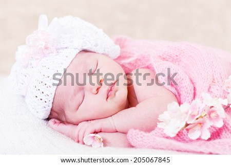 newborn girl sleeps with spring flowers under a knitted pink cape