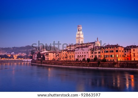 Night view of  Adige River and riverside apartments. Verona Cathedral and Castel San Pietro are also visible. - stock photo